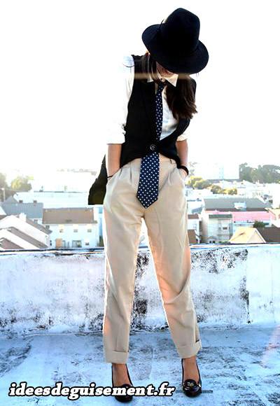 Femme modèle chic en pantalon et chemiser avec cravate et chapeau
